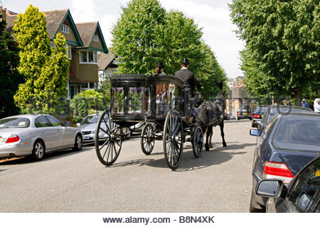 An old fashioned horse drawn hearse in a north London street - Stock Photo