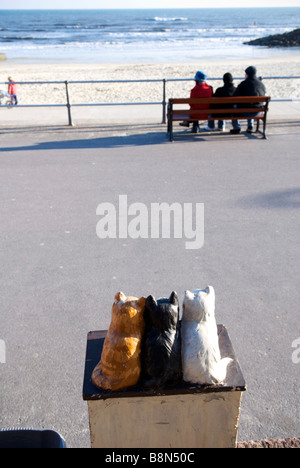 close up of rear view of three ceramic cats on charity box with three people on bench on promenade in background - Stock Photo