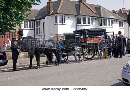 An old fashioned horse-drawn hearse in a north London street for the funeral for an Indian family - Stock Photo