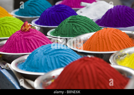 Metal containers filled with coloured Indian rice powder used for making rangoli designs at Indian festivals - Stock Photo