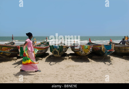 fish boats on the beach with woman in pink traditional dress walking casamance cap skirring - Stock Photo