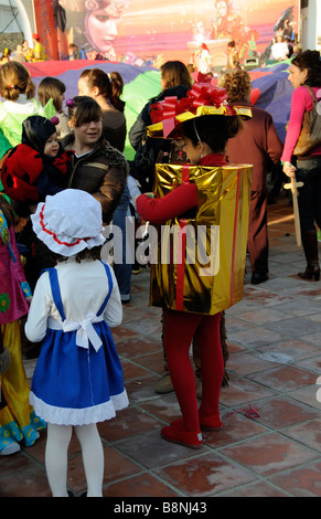 Little girl in fancy dress as a gold package present wrapped in red ribbon. A contestant in annual carnival at La - Stock Photo