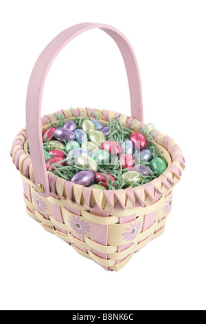 A pretty easter basket filled with chocolate candy eggs Isolated with clipping path included - Stock Photo