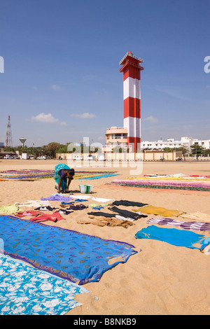 India Tamil Nadu Chennai woman drying colourful laundry on beach below the lighthouse - Stock Photo