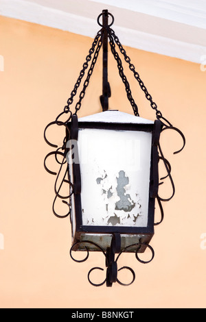 Classical forged hanging lantern in winter covered with snow. - Stock Photo