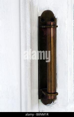 Old classic brass door knob on white painted door closeup. - Stock Photo