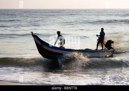 India Tamil Nadu Mamallapuram fishing village fishermen returning to shore in tsunami relief boat - Stock Photo