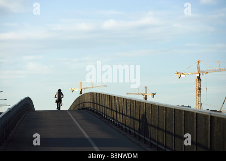 Sweden, Stockholm, bicyclist riding over bridge, cranes in background - Stock Photo