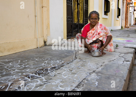 India Pondicherry woman decorating pavement outside doorway with traditional rice water New Year pattern - Stock Photo