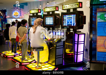 arab man playing on slot machine in amusement arcade, dubai, uae - Stock Photo