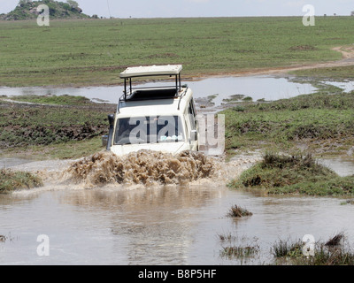 Africa Tanzania Serengeti National Park Safari tourists in an open top land rover crossing a water barrier - Stock Photo