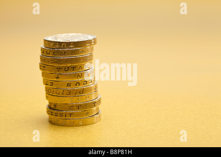 Stack of £1 one pound coins sterling on gold background - Stock Photo