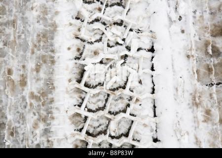 tyre tread tracks in snow - Stock Photo