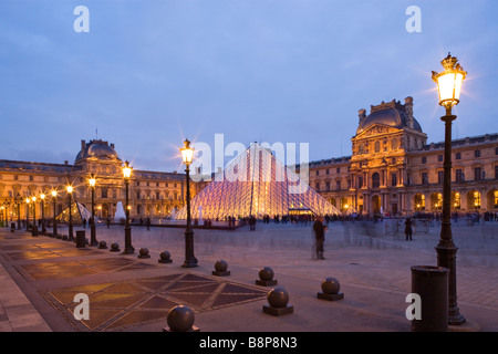 The Louvre Museum illuminated glass pyramid entrance Paris France - Stock Photo