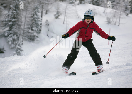 Young novice skier doing snowplough turn skiing downhill with fresh snowfall on ski slope piste in Austrian Alps - Stock Photo