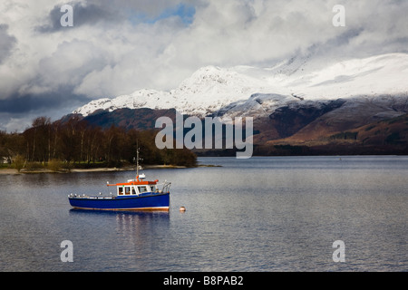 Small boat on Loch Lomond with Ben Lomond snow covered in the background, Scotland, UK - Stock Photo