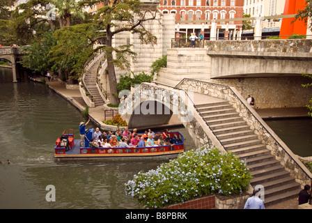 San Antonio River Walk texas tour boat passing under bridge one level below street traffic - Stock Photo