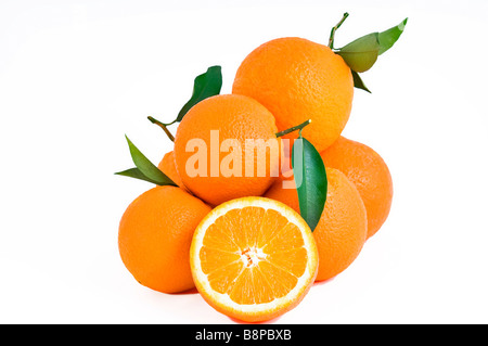 Pile of fresh juicy oranges with green leaves isolated on white background and one cut orange - Stock Photo