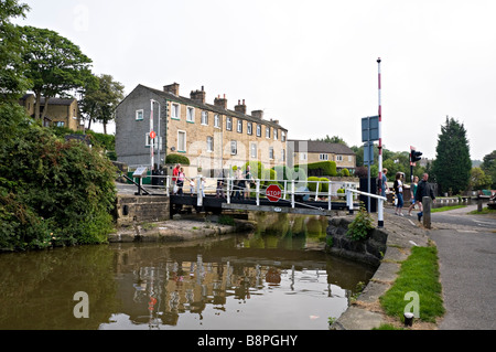 People crossing Brewery swing bridge near Skipton on the Leeds to Liverpool canal - Stock Photo