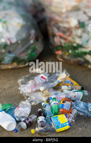 Crushed plastic bottles on ground, garbage bags in background - Stock Photo