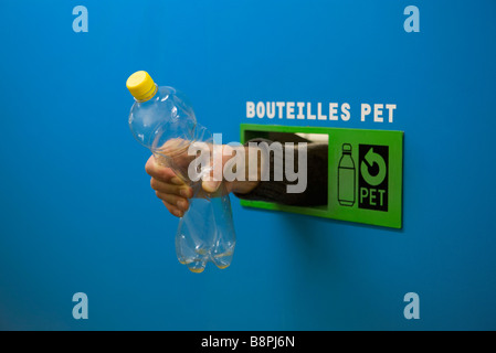 Hand reaching from inside recycling receptacle, holding plastic bottle - Stock Photo