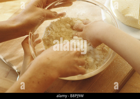 Parent and child mixing ingredients in bowl with hands - Stock Photo