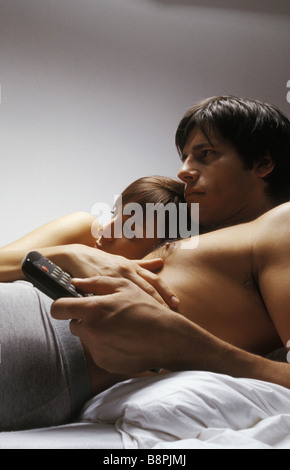 Young couple lying together in bed watching television - Stock Photo
