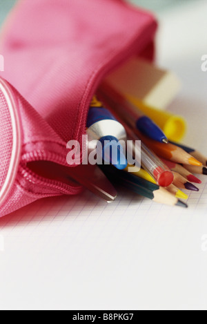Colored pencils spilling out of pencil case - Stock Photo
