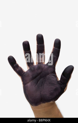 Man's hand with black paint on palm - Stock Photo