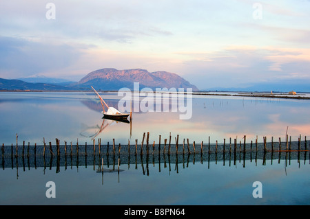 Landscape at sunrise in Mesologi- small wooden white fishing boat lays on the calm waters in the lagoon. - Stock Photo