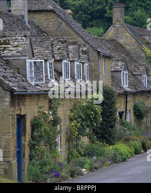 Row of cottages in the village at Snowshill with roses tumbling over the windows and doorways - Stock Photo