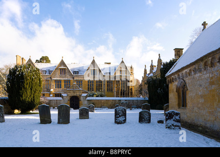 Winter snow at St Peters church and Stanway Manor in the Cotswold village of Stanway, Gloucestershire - Stock Photo