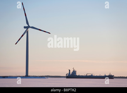 Cargo ship on frozen sea passing a big WinWind 3 MW wind turbine , Oulu , Finland - Stock Photo