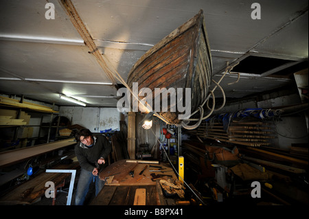 Boatbuilder and repairer Ryan Kearley planing some wood in his Barcombe workshop Sussex UK - Stock Photo