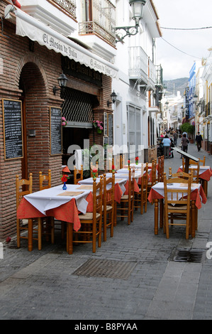 Empty restaurant and unoccupied tables laid up and ready for custom on a street in the town of Nerja southern spain - Stock Photo
