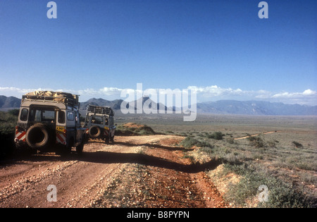Two Landrovers on the road to South Horr from Baragoi in northern Kenya East Africa - Stock Photo