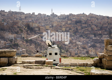 A modern TV van seen in the ancient Citadel of Amman, Jordan, with the city in the background - Stock Photo
