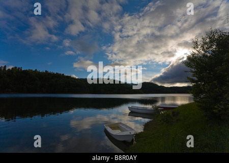 Serene late afternoon scene on peaceful lake, three moored boats peaceful serene serenity - Stock Photo