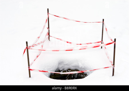 Open sewer manhole in winter covered with snow. - Stock Photo