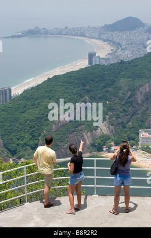 TOURISTS VIEW RIO DE JANEIRO FROM  SUGARLOAF MOUNTAIN LOOKING TOWARDS COPACABANA BEACH - Stock Photo