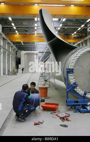 Workers next to a giant wind turbine blade at the factory VentoMoinho at Viana do Castelo, Portugal. - Stock Photo