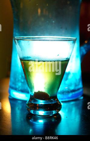 Cocktails on a dark nightclub bar top at night.  Drinking in a bar or nightclub. - Stock Photo