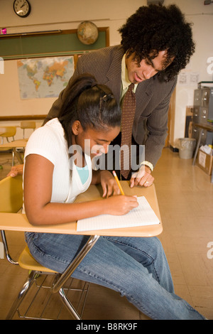 african american teacher in public american school helps teenage student solve a problem at her desk in classroom - Stock Photo