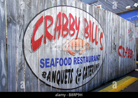Painted wood fence panel sign for Crabby Bills Restaurant in Clearwater Beach Florida USA - Stock Photo