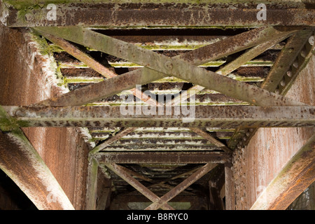 Latticed rusted metal beams forming old bridge decking. - Stock Photo