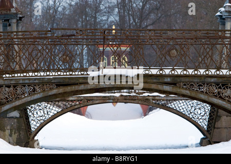Two weathered metal forged arch bridges covered with snow in winter park. - Stock Photo