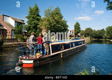 A narrow boat glides along the Regent Canal near Mile End and Victoria Park in east London, England - Stock Photo