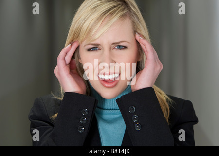 Close up studio shot of a stressed businesswoman holding her head in pain - Stock Photo