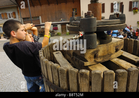 Two Swiss boys operate an old wine press at a wine festival - Stock Photo