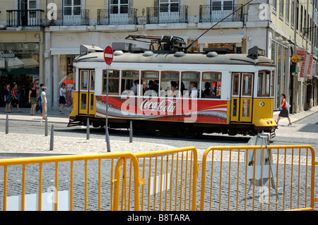 A tram carrying a few passengers and advertising Coca-Cola passes a corner of Rossio Square, Lisbon - Stock Photo